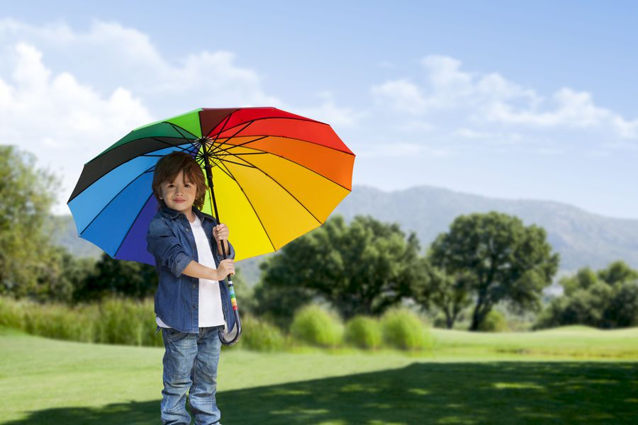 Young boy with umbrella in nature on green grass